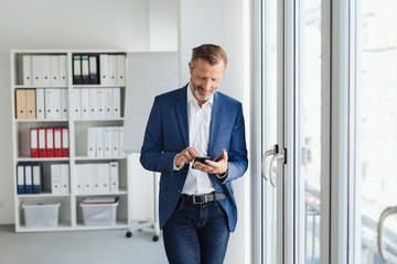Confident businessman using a mobile in the office Wall mural