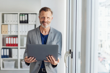 Smiling professional man holding an open laptop