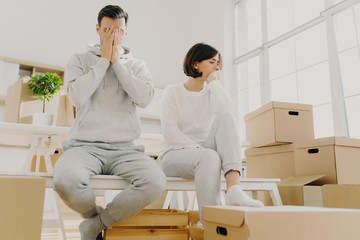 Worried couple pose near stack of cardboard boxes, have to move in other flat, have no money for rent, have dejected sad expressions, sit together in white room, have family conflict and divorce
