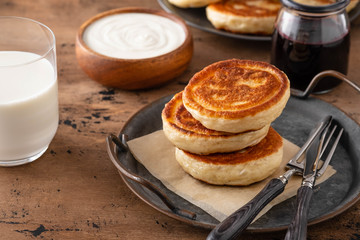 Homemade pancakes stack with milk and jam on wooden background.