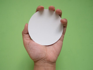 Woman hand holding white circle paper. Isolated in green background.