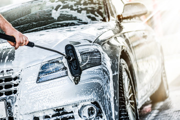 Manual car wash with brush and pressurized water in automobile washing station. Cleaning front...