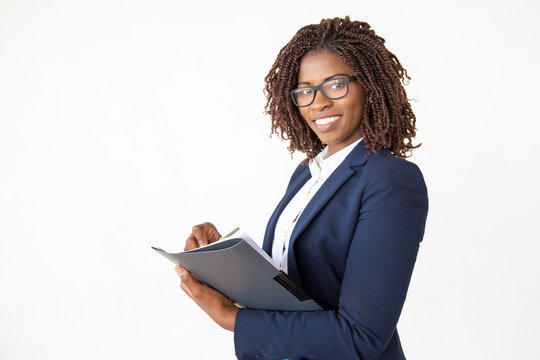 Happy expert checking documents, taking notes in paper, holding pen and folder. Young African American business woman posing isolated over white background. Paperwork concept