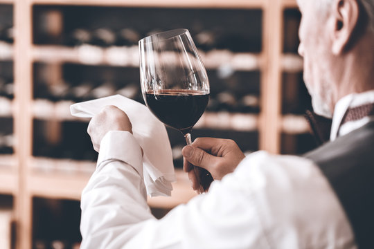 Sommelier Concept. Senior man standing wiping glass of wine diligently back view close-up