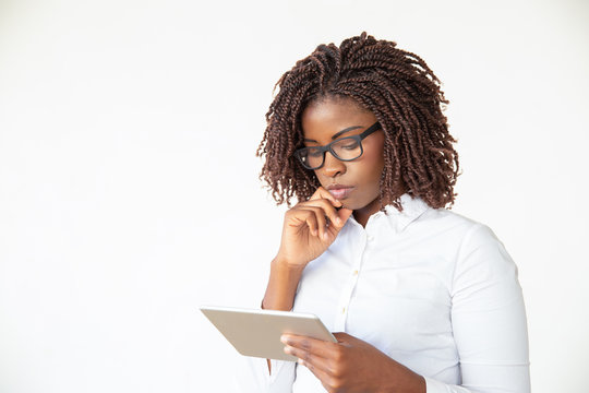 Serious focused manager watching presentation on tablet. Young African American female professional standing isolated over white background. Digital device using concept