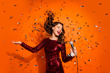 Portrait of positive cheerful girl enjoy bachelor party celebration sing song in karaoke hold microphone wear burgundy red clothes isolated over orange color background confetti hair flying falling