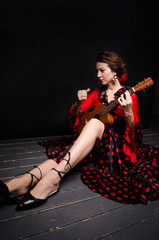 Carmen beautiful woman in red dress, with guitar on dark background sitting on the floor