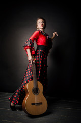 Carmen beautiful woman in red dress, with guitar on dark background
