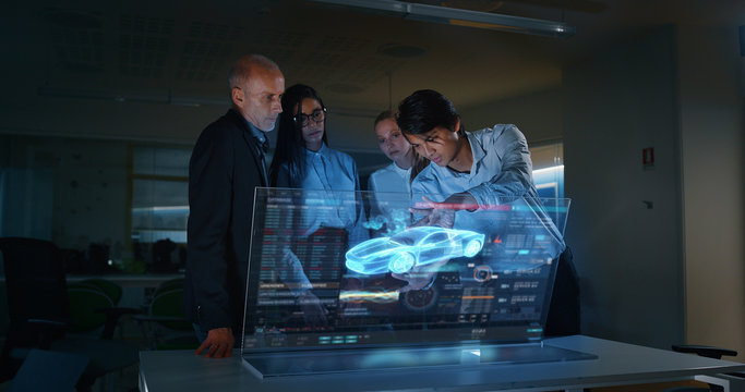 A group of modern engineers are designing an electric car by using futuristic sophisticated technology screen with augmented reality holograms in a creative studio.