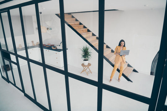 Above high angle full length body size view of nice attractive trendy lady using laptop creating new launch start-up booking rent house flat in modern style light white interior apartment