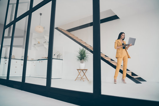 Full length body size view of nice attractive trendy focused smart lady using laptop searching new real estate service creating start-up booking house in modern style light white interior apartment