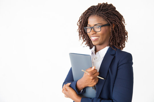 Happy cheerful office assistant in glasses holding documents, looking away, smiling. Young African American business woman posing isolated over white background. Corporate portrait concept