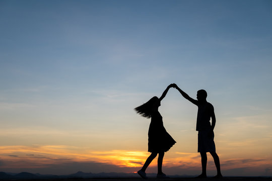 A silhouette of a happy young couple slow dancing outside at sunset, with copy-space in sky.