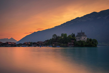 Sunset above Iseltwald peninsula and former castle in Switzerland