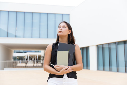 Pensive female intern carrying documents. Young Asian woman walking outside, holding notebook and folder with papers. Career beginning concept