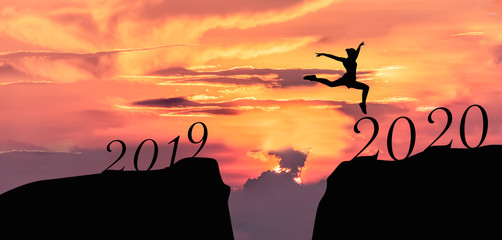 Happy new year 2020, Silhouette of 2020 letters on the mountain with business people jump across gap of mountain at sunrise.