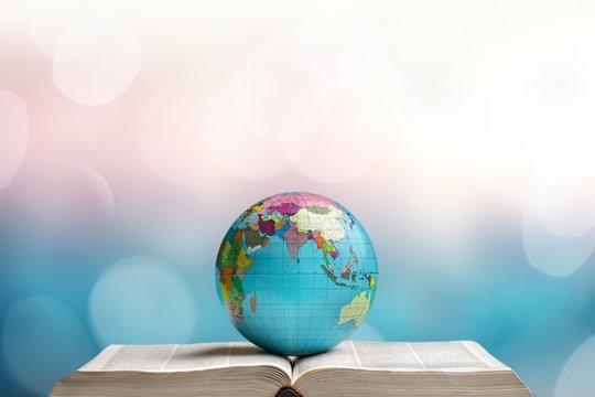 Heavy open book and globe on abstract background