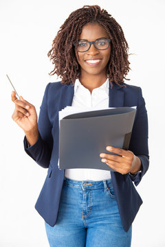 Happy confident business coach wearing glasses, holding pen and documents, looking at camera. Young African American business woman posing isolated over white background. Trainer concept