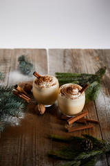 eggnog cocktail with whipped cream and cinnamon near spruce branches and powdered sugar scattered...