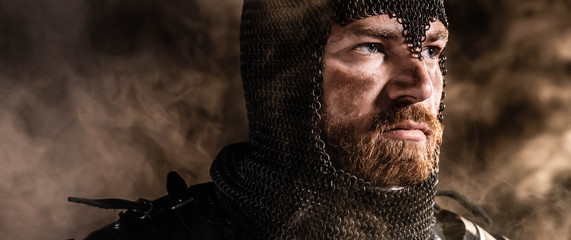 panoramic shot of handsome knight in armor looking away on black background