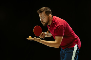 Wall Mural - Young man plays table tennis on black studio background. Model in sportwear plays ping pong. Concept of leisure activity, sport, human emotions in gameplay, healthy lifestyle, motion, action, movement
