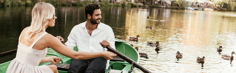 panoramic shot of young couple in boat on lake near flock of ducks