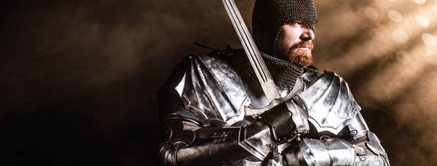 panoramic shot of handsome knight in armor holding sword on black background