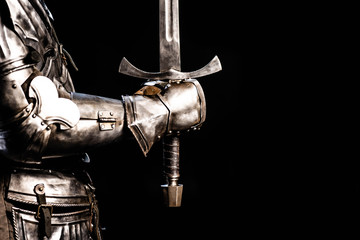 Tuinposter Paarden cropped view of knight in armor holding sword isolated on black
