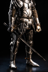 cropped view of knight in armor holding sword on black background