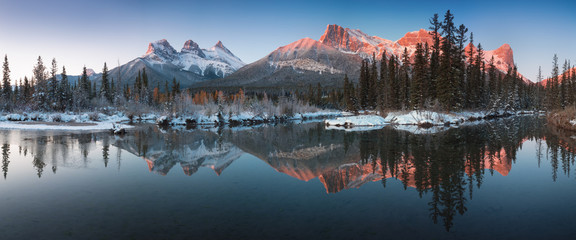 Almost nearly perfect reflection of the Three Sisters Peaks in the Bow River. Near Canmore, Alberta Canada. Winter season is coming. Bear country. Beautiful landscape background concept.