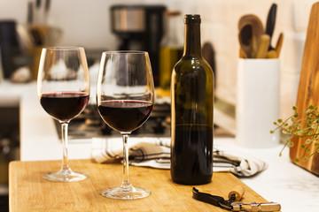 Copas con vino tinto y botella sobre tabla de madera rústica en la cocina