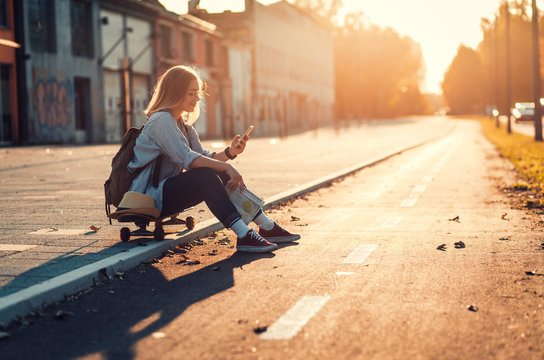 Smiling girl sitting on long board in the city during sunset and looking at phone.