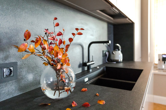 Wooden grey kitchen room organization. Pure water and clear sink with fall decor