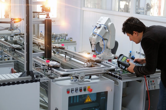 Man is holding teach panel to control a robotic arm which is integrated on smart factory production line. industry 4.0 automation line which is equipped with sensors and robotic arm. Selective Focus.