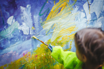 Smart little girl drawing on the wall. little girl child stained in paint and a dressing gown draws with a brush using watercolor on the wall. drawing room lesson classes in school or kindergarten