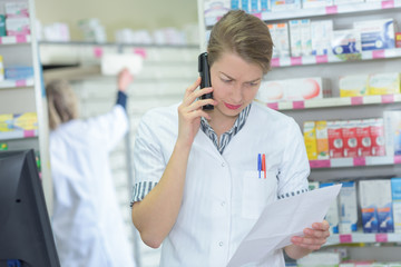 pharmacist reading the list on the telephone