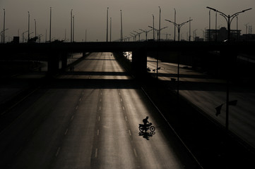 A man walks with his motorbike on a deserted road, leading towards the venue of what participants call Freedom March in Islamabad