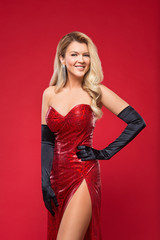 portrait of a beautiful girl with long, blond hair in a red dress on a red background