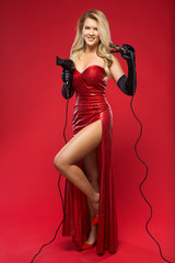 girl hairdresser with a curling iron and a hairdryer in hands in a red dress on a red background