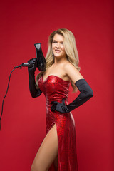 girl hairdresser with a hairdryer in hands in a red dress on a red background