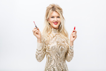 girl in a brilliant dress holds lipstick in her hands isolated on a white background