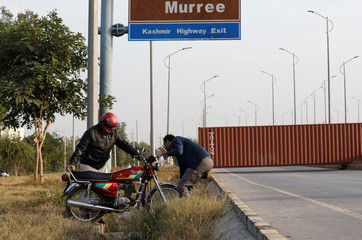 A man helps another bring his motorbike across the road near a shipping container used to block the road leading towards red zone, before what participants call a Freedom March in Islamabad