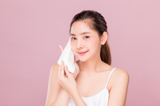 Young attractive Asian woman using hygiene wiper sheet to clean her face skin isolated on pink.