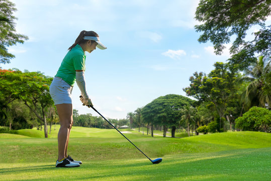 Healthy Sport. Asian Sporty woman golfer player doing golf swing tee off on the green , people presumably does exercise. Healthy Lifestyle Concept.