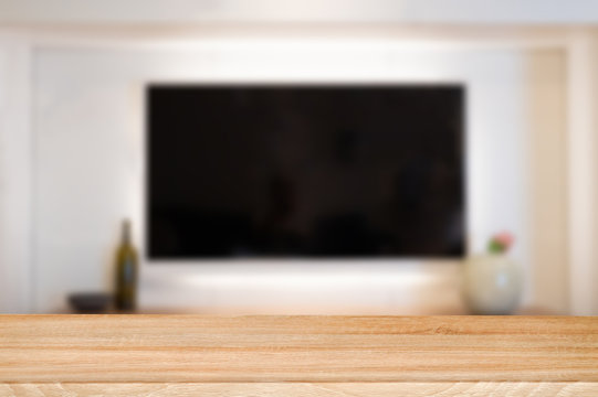 empty wooden table top with tv in living room blurred background.