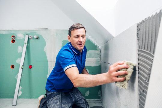 Fliesenleger in einem modernem badezimmer verlegt fliesen platten