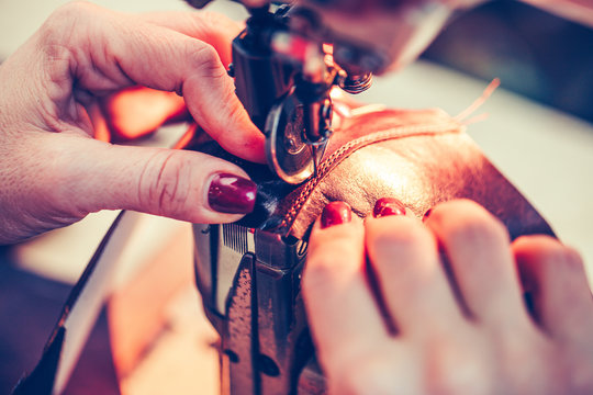 Female hands sewing leather shoes in the handmade footwear industry