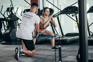 back view of personal trainer supervising young sportswoman exercising with resistance band