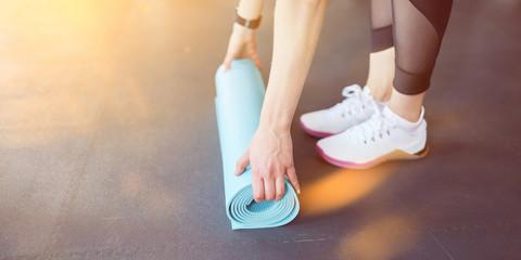 Frau rollt Yogamatte auf nach Wellness Übung