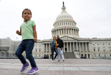 A child plays as her parents pose for a photograph in front of the Capitol in Washington